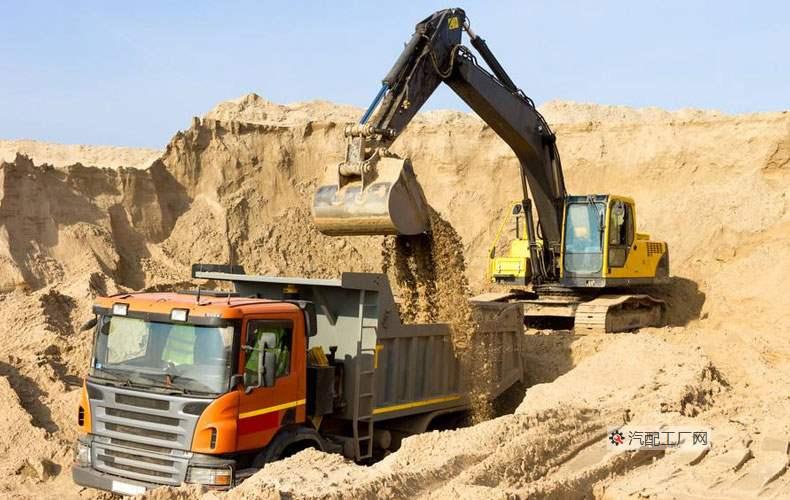 工地挖掘机正在为自卸运输车装货